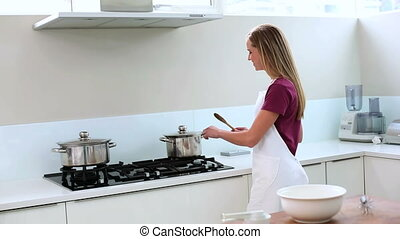 Blonde woman preparing meal in kitchen at home