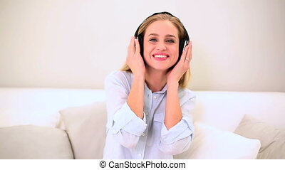 Blonde woman listening music and dancing on sofa at home