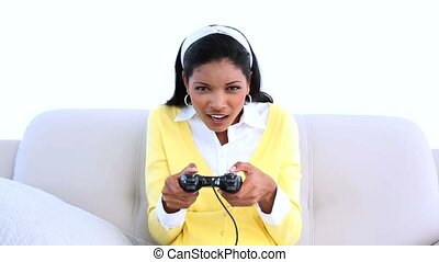 Woman playing video games on sofa at home