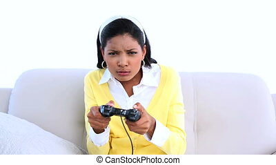 Concentrated woman playing video games on sofa at home