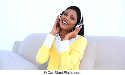 Woman wearing headphones for listening music on sofa at home