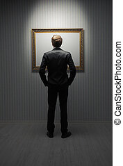 Modern art - A young man standing in front a empty frame in...