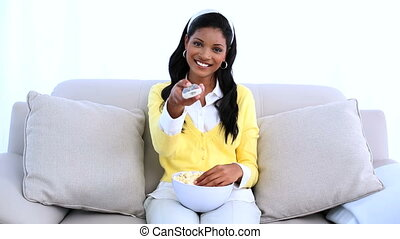 Smiling woman sitting on sofa changing channel of television...