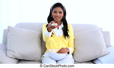 Woman sitting on sofa changing channel of television and...