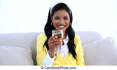 Woman sitting on sofa drinking white wine at home