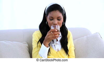 Smiling woman sitting on sofa drinking white wine at home