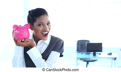 Smiling businesswoman checking piggy bank in office