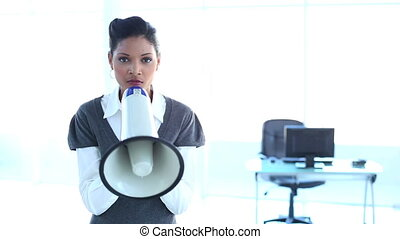 Serious businesswoman screaming in a megaphone in office