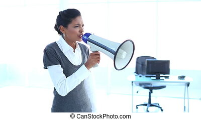 Furious businesswoman screaming in a megaphone in office