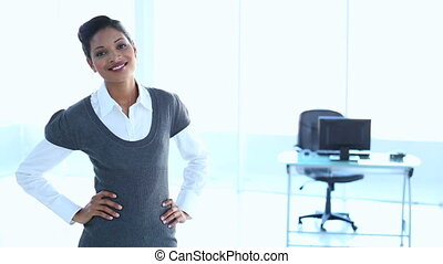Businesswoman put hands on her hips in office