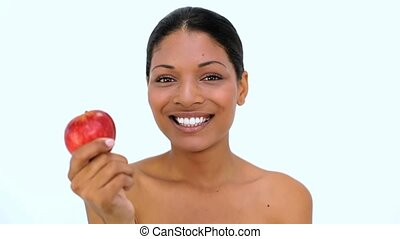 Happy woman showing red apple at camera on white background