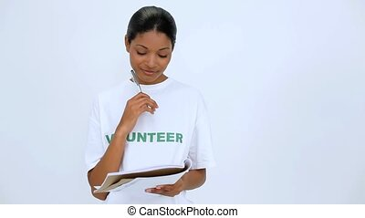 Smiling volunteer woman thinking and writting on notebook on...