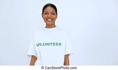 Smiling volunteer woman does a thumbs up at camera on white...