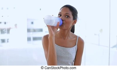 Beautiful woman drinking water on her flask in apartment