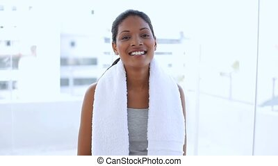 Beautiful woman with towel drinking water on her flask in...