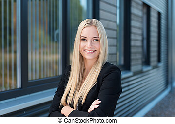 Happy confident young businesswoman standing outside her...