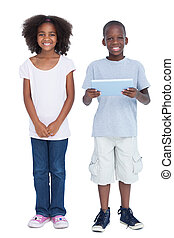 Smiling boy holding tablet pc with his sister next to him
