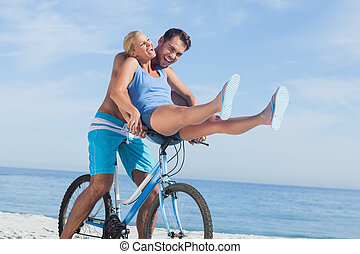 Happy man giving girlfriend a lift on his crossbar of bike...