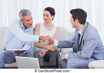 Salesman closing a deal with a smiling couple sitting on...