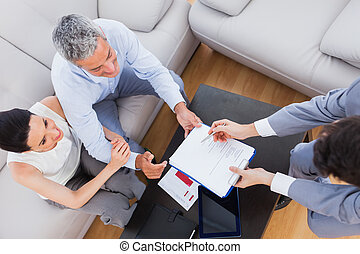 Salesman showing contract to couple sitting on couch at home