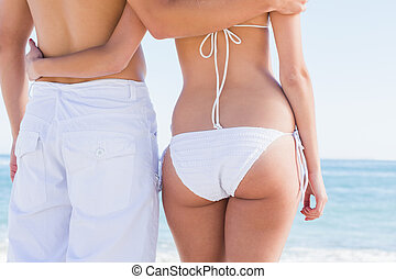 Rear mid section of fit couple facing the sea at the beach
