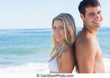 Young smiling couple standing back to back at the beach