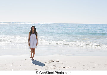 Brunette in white sun dress walking from the sea on the...