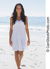 Smiling brunette in white sun dress walking towards camera...