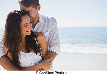 Attractive couple cuddling at the beach