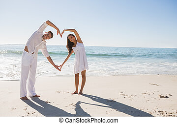 Loving couple forming heart shape with arms at the beach
