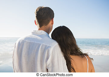 Peaceful couple looking at the ocean at the beach
