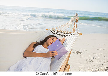 Woman lying on hammock reading book on the beach
