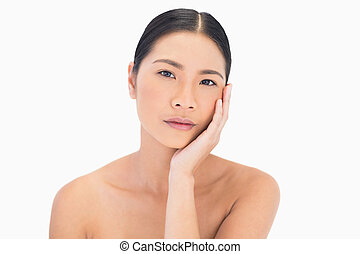 Natural model posing touching her cheek on white background
