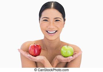 Smiling natural brunette holding apples in both hands on...