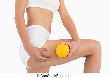 Slender female body holding orange and squeezing her thigh...