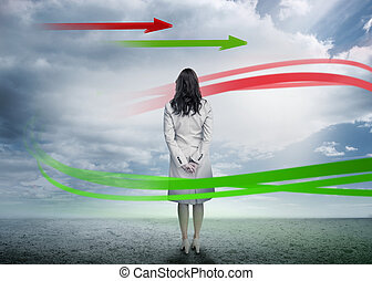 Businesswoman looking at arrows