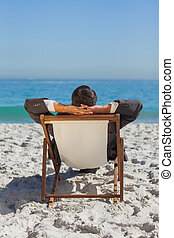 Relaxed young businessman resting on his sun lounger on the...