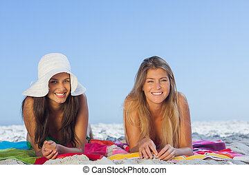 Two smiling friends lying on the sand having holidays...