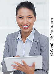 Smiling businesswoman posing scrolling on her tablet pc -...