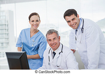 Cheerful doctors and surgeon looking at camera while working...