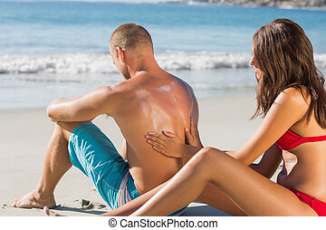 Smiling woman putting sun cream on her boyfriends back -...