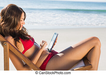 Attractive woman on the beach using her tablet while...