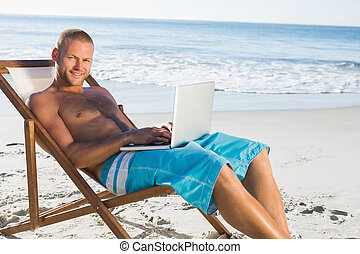 Smiling handsome man on the beach using his laptop while...