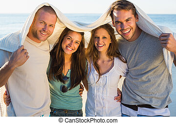 Happy group of friends having fun together on the beach