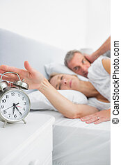 Tired wife turning off alarm clock as husband is covering...
