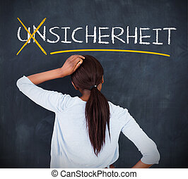 Woman looking at a chalkboard with sicherheit on it in white...