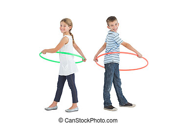 Brother and sister playing with hula hoop together on white...