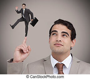 Businessman showing shrunk colleague dancing on his finger -...