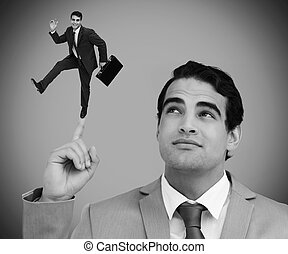 Thoughtful businessman showing shrunk colleague dancing -...