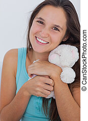 Young woman hugging a small teddy bear